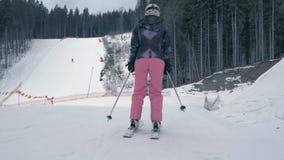 Turista femminile che spinge fuori con i bastoni e che scia nei Carpathians nel slo-Mo archivi video