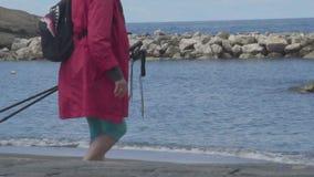 Turista femminile con l'escursione dei pali a disposizione che fa un passo - giù al litorale, viaggio stock footage