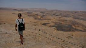 Turista femminile con lo zaino che cammina lungo il bordo della scogliera della roccia della montagna stock footage