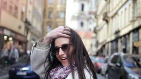 Turista femminile elegante felice che si muove sulla via occupata della città che gira mano intorno d'ondeggiamento archivi video