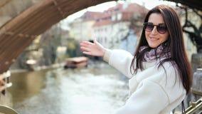Turista femminile sorridente attraente che ammira vista stupefacente del fiume dall'argine della città archivi video