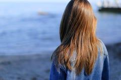 Turista grazioso che sta sulla spiaggia e sviluppa i capelli, en della ragazza Fotografie Stock Libere da Diritti