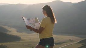 Turista hermoso de la muchacha que mira un mapa mientras que se coloca al borde de una montaña durante puesta del sol metrajes