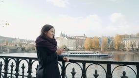 Turista hermoso de la mujer joven en Praga usando su Smartphone, concepto que viaja metrajes