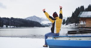Turista hermoso del día de invierno que se sienta en el barco azul por otra parte de la orilla del lago y admirar el paisaje de l almacen de video