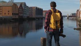 Turista hermoso joven atractivo con una mochila amarilla que camina en el centro de ciudad y que toma una foto, cámara lenta almacen de video