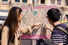 Turista joven de los pares que mira el mapa y direcciones de la ciudad juntas imagenes de archivo