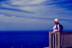 Turista joven del concepto del viaje que mira la opinión hermosa del mar Foto de archivo