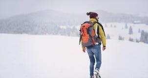 Turista joven equipado que camina a través de campo nevoso, él va a su destino en el top de la montaña, sorprendiendo paisaje metrajes