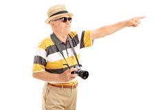Turista maduro que aponta em algo com mão fotos de stock