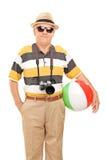 Turista maduro que guarda uma bola de praia Fotos de Stock