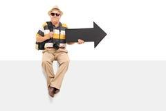 Turista maduro que sostiene una flecha asentada en el panel Imágenes de archivo libres de regalías