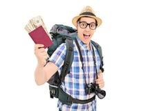 Turista maschio che giudica il suo passaporto pieno di soldi Immagini Stock