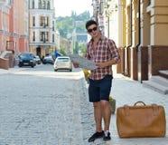 Turista maschio con una valigia e un programma Fotografie Stock Libere da Diritti