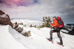 Turista maschio in racchette da neve della neve Fotografia Stock