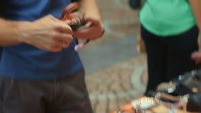 Turista maschio sorridente sulla vacanza che esamina le scarpe di cuoio fatte a mano il mercato archivi video