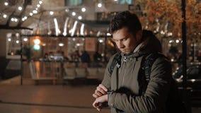 Turista masculino com smartwatch na rua da noite, olhando relógio ausente e tocante Fotos de Stock