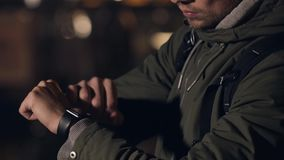 Turista masculino com smartwatch na rua da noite, olhando relógio ausente e tocante Foto de Stock