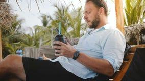 Turista masculino feliz bem sucedido com relógio esperto e o suco de fruta que sentam-se na cadeira de praia usando o app da comp video estoque