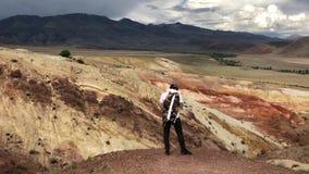 Turista masculino joven que admira las montañas hermosas montañas rojas hermosas de Altai Reserva natural de la montaña Altai almacen de metraje de vídeo