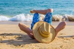 Turista masculino joven que toma el sol en la playa en el mar Imágenes de archivo libres de regalías