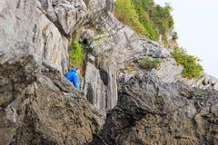 Turista masculino louro branco em um casaco azul nas rochas em Vietname fotos de stock