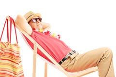 Turista masculino maduro que goza en una silla de playa Imágenes de archivo libres de regalías