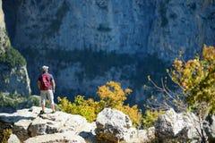 Turista masculino novo no desfiladeiro de Vikos, um desfiladeiro nas montanhas de Pindus de Grécia do norte, encontrando-se nas i imagens de stock