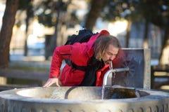 Turista masculino que bebe el agua mineral de la fuente de la ciudad en el pueblo de Mestia en día soleado frío en último otoño Foto de archivo libre de regalías