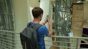 Turista masculino que toma a imagem da construção de vidro contemporânea em seu smartphone video estoque