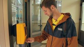 Turista masculino que valida el boleto funicular, pago para el viaje, transporte público almacen de metraje de vídeo