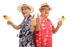 Turista mayor con los cócteles que hacen el pulgar encima de gestos Fotografía de archivo
