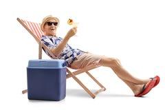 Turista mayor con un cóctel que se sienta en una silla de cubierta al lado de Fotografía de archivo libre de regalías