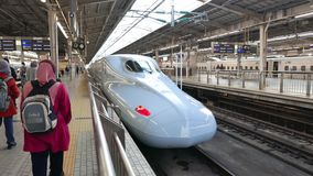 Turista muçulmano na frente de uma série de Shinkansen N700A video estoque