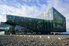 Turista não identificado que anda em torno da sala de concertos e do centro de conferências de Harpa em Islândia Foto de Stock