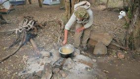 Turista no acampamento agitado com uma colher para cozinhar Pasta In uma caçarola no fogo filme