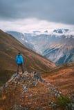 Turista no casaco azul que está em uma rocha nas montanhas Fotografia de Stock