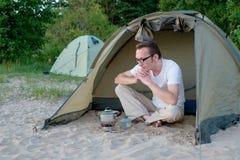 Turista novo que espera seu jantar no acampamento no queimador de gás Fotografia de Stock