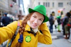 Turista novo que toma um selfie durante a parada do dia do St Patrick anual em New York Fotografia de Stock