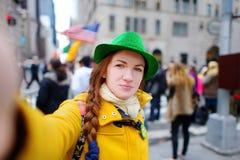 Turista novo que toma um selfie durante a parada do dia do St Patrick anual em New York Fotos de Stock