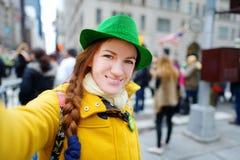 Turista novo que toma um selfie durante a parada do dia do St Patrick anual em New York Foto de Stock