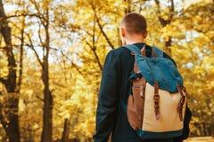 Turista o viaggiatore con uno zaino nella foresta di autunno immagine stock