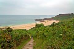 Turista que camina abajo de las escaleras con los helechos a la playa de Erquy Foto de archivo