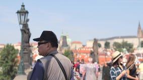 Turista que camina en Charles Bridge icónico metrajes