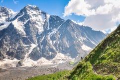 Turista que camina en una cuesta escarpada en un fondo de la montaña foto de archivo libre de regalías