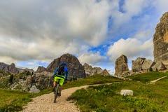 Turista que completa un ciclo en el ` Ampezzo de la cortina d, aturdiendo a Cinque Torri y fotos de archivo