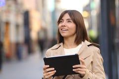 Turista que consulta una guía en una tableta y que mira la calle Foto de archivo libre de regalías