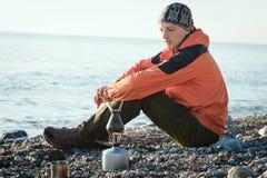 Turista que cozinha o café fresco da manhã pelo mar no fogo da tocha Foto de Stock Royalty Free