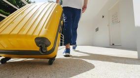 Turista que deja el apartamento moderno con una maleta amarilla metrajes