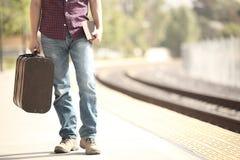 Turista que espera en una estación de tren Foto de archivo libre de regalías